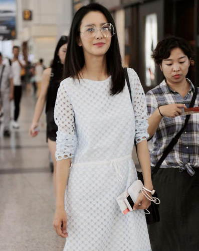 佟丽娅连身裙现身机场 露招牌笑容酒窝抢镜