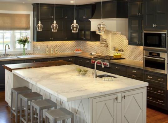 图片上面为我们展示的是吧台与厨房结合的一个空间,淳朴古典的黑色大型转角橱柜,看起来是相当的大气华丽,吧台的外形比较巨大,在厨房可是有着举足轻重的地位。吧台采用了素白色的大理石,上面有着淡淡的灰色纹理,美观大方,吧台同时还安装了一个洗水池。   大理石吧台图片:古典之范