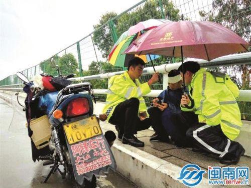 暖心!晋江交警暴雨中为摔倒司机撑伞