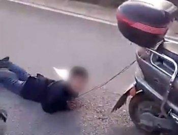 """为""""吓唬""""孩子 母亲把他拴摩托车后"""